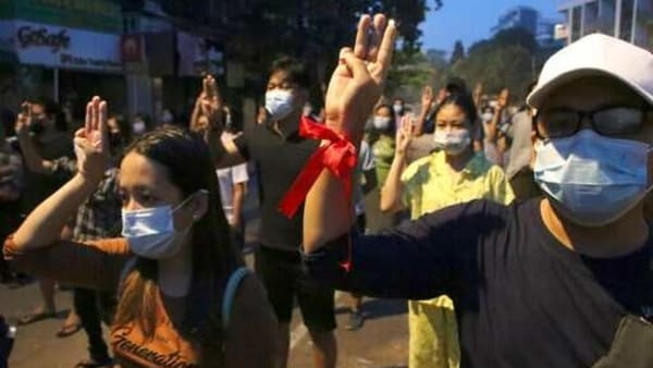 Anti-coup protesters flash three-fingered gesture, a symbol of resistance, during a rally outside their homes in downtown Yangon, Myanmar, Monday morning, March 22, 2021.