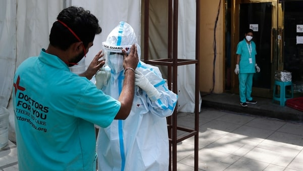 FILE PHOTO - In this April 19, 2021, file photo, a health worker adjusts the face shield of another as she prepares to go inside a quarantine center for COVID-19 patients in New Delhi, India.