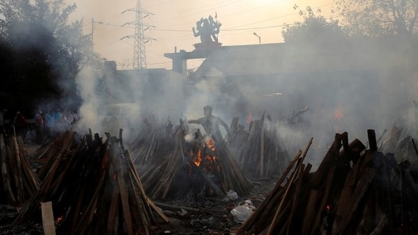 A man performs last rites next to the funeral pyres of those who died from the coronavirus disease (COVID-19), during a mass cremation at a crematorium in New Delhi, India May 1, 2021.