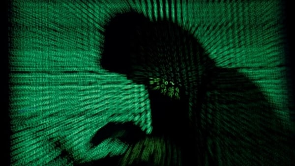 FILE PHOTO: A hooded man holds a laptop computer as cyber code is projected on him in this illustration picture taken on May 13, 2017. Top U.S. fuel pipeline operator Colonial Pipeline has shut its entire network after a cyber attack, the company said on Friday.