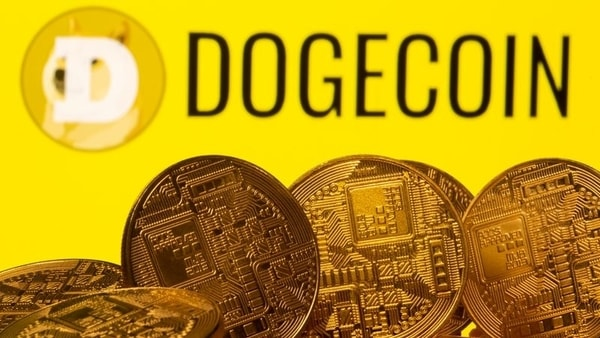 FILE PHOTO: Cryptocurrency representations are seen in front of the Dogecoin logo in this illustration picture taken April 20, 2021.