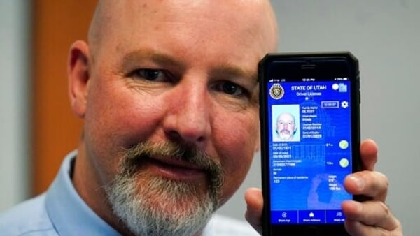 Ryan Williams, with the Utah Drivers License Division, displayes his cell phone with the pilot version of the state's mobile ID on Wednesday, May 5, 2021, in West Valley City, Utah. The card that millions of people use to prove their identity to everyone from police officers to liquor store owners may soon be a thing of the past as a growing number of states develop digital driver's licenses. In Utah, over 100 people have a pilot version of the state's mobile ID, and that number is expected to grow to 10,000 by year's end. Widespread production is expected to begin at the start of 2022. (AP Photo/Rick Bowmer)