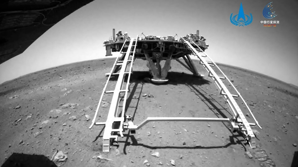 In this image released by the China National Space Administration (CNSA) on Saturday, May 22, 2021, a landing platform and the surface of Mars are seen from a camera on the Chinese Mars rover Zhurong. China's first Mars rover has driven down from its landing platform and is now roaming the surface of the red planet, China's space administration said Saturday.