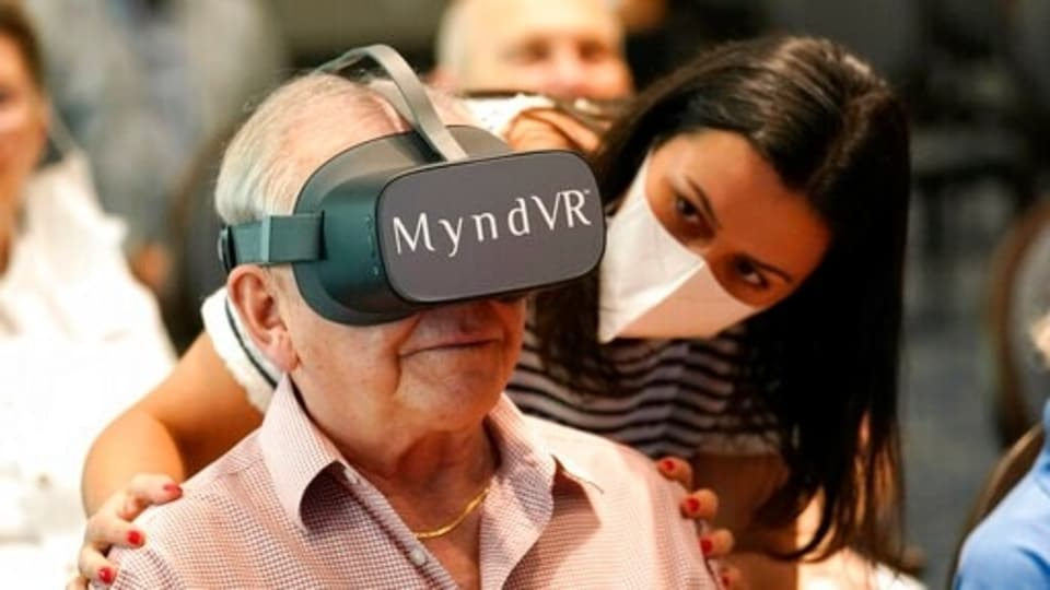 Gloria Gantes, right, monitors Terry Colli, a resident of John Knox Village, as he participates in a virtual reality study, Tuesday, June 1, 2021, in Pompano Beach, Fla. The senior community is in partnership with Stanford University's Virtual Human Interaction Lab on a study to see how older adults respond to virtual reality and whether it can improve their sense of wellbeing. (AP Photo/Lynne Sladky)