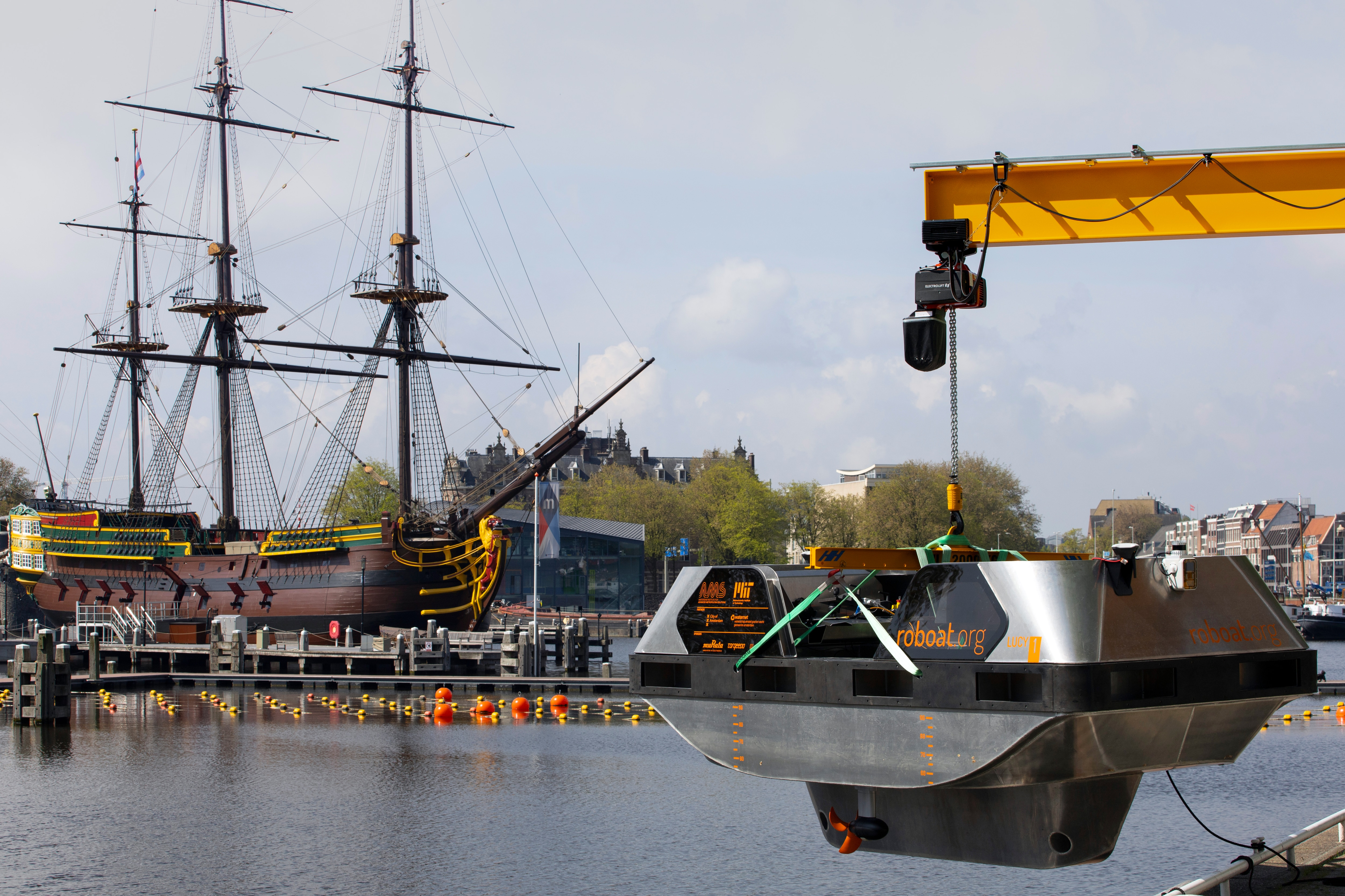 An electric boat is lowered outside a workshop with a full-size replica of the 18th century three-mast trading ship Amsterdam at the National Maritime Museum in the background, in Amsterdam, Thursday, May 20, 2021. Already steeped in maritime history, the city's more than 100 kilometers (60 miles) of waterways are to start hosting prototypes of futuristic boats — small, fully-autonomous electric vessels — to carry out tasks including transporting passengers and picking up garbage. (AP Photo/Peter Dejong)