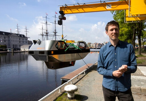 Stephan van Dijk, Director of Innovation at the Advanced Metropolitan Solutions institute, is interviewed with an electric boat in the background, in Amsterdam, Thursday, May 20, 2021. Already steeped in maritime history, the city's more than 100 kilometers (60 miles) of waterways are to start hosting prototypes of futuristic boats — small, fully-autonomous electric vessels — to carry out tasks including transporting passengers and picking up garbage. (AP Photo/Peter Dejong)