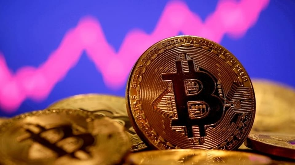 FILE PHOTO: A representation of virtual currency Bitcoin is seen in front of a stock graph in this illustration taken January 8, 2021. REUTERS/Dado Ruvic