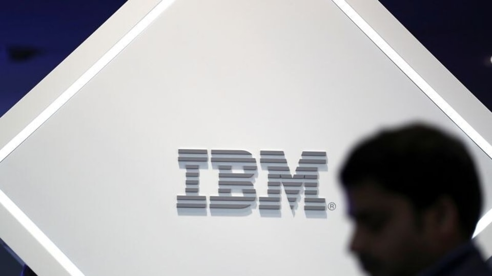FILE PHOTO: A man stands near an IBM logo at the Mobile World Congress in Barcelona, Spain, February 25, 2019.