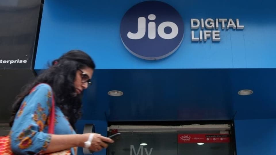 A woman checks her mobile phone as she walks past a mobile store of Reliance Industries' Jio telecoms unit, in Mumbai, India, July 11, 2017. REUTERS/Shailesh Andrade/Files