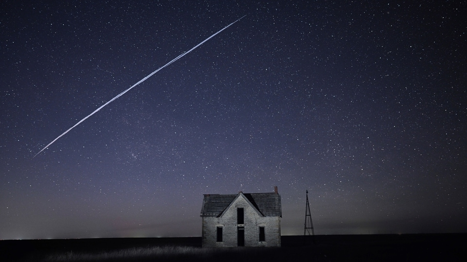 In this photo made with a long exposure, a string of SpaceX StarLink satellites passes over an old stone house near Florence, Kan., on Thursday, May 6, 2021.