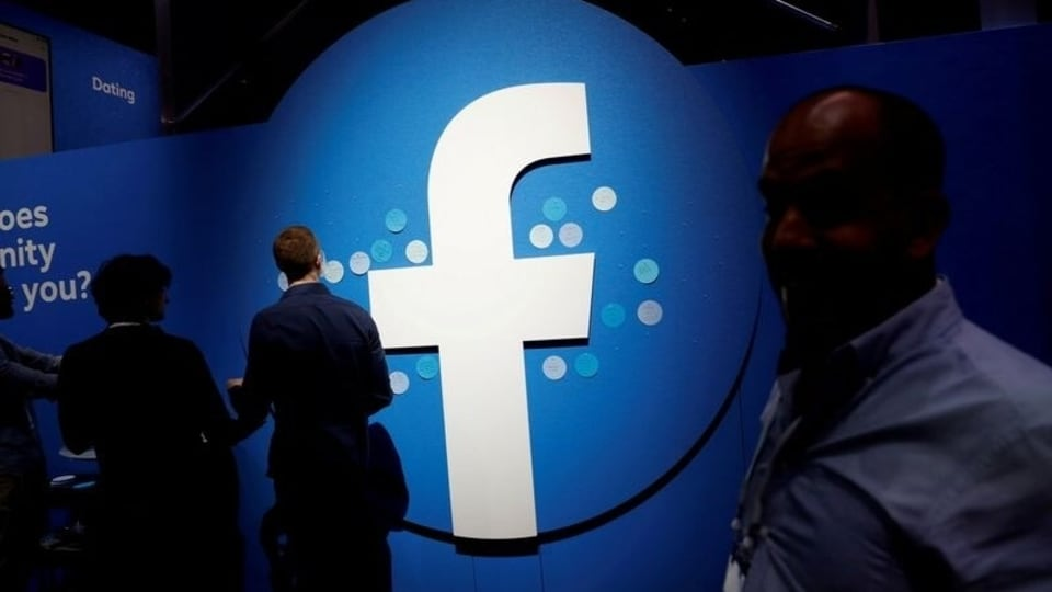 FILE PHOTO: Attendees walk past a Facebook logo during Facebook Inc's F8 developers conference in San Jose, California, U.S., April 30, 2019.