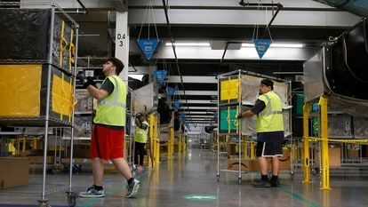 FILE - In this Dec. 17, 2019, file photo, Amazon workers move containers to delivery trucks at an Amazon warehouse facility in Goodyear, Ariz. Starting Monday, Aug. 9, 2021, Amazon will be requiring all of its 900,000 U.S. warehouse workers to wear masks indoors, regardless of their vaccination status. The move follows steps by a slew of other retailers, including Walmart and Target, to mandate masks for their workers. In many of those cases the mandates apply to workers in locations of substantial COVID-19 transmission (AP Photo/Ross D. Franklin, File)