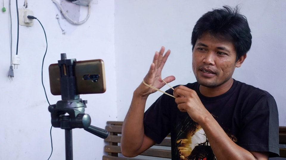 This picture taken on June 20, 2021 shows Indonesian YouTuber Siswanto recording one of his videos at his home in a farming community in Banyuwangi. - Siswanto was a down-on-his-luck mechanic until his improbable pivot to internet videos turned his neighbours into stars and vaulted his poor farming community into the limelight as Indonesia's