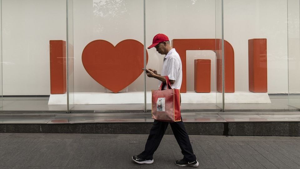 A pedestrian in front of a Xiaomi Corp. store in Shanghai, China, on Tuesday, Aug. 24, 2021. Photographer: Qilai Shen/Bloomberg