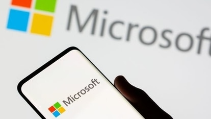 A smartphone is seen in front of a Microsoft logo displayed in this illustration.