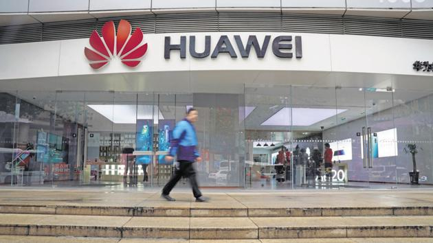 A man walks by a Huawei logo at a shopping mall in Shanghai, China December 6, 2018.