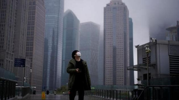A man wearing a protective face mask is seen following an outbreak of coronavirus (COVID-19), at Lujiazui financial district in Shanghai, China.