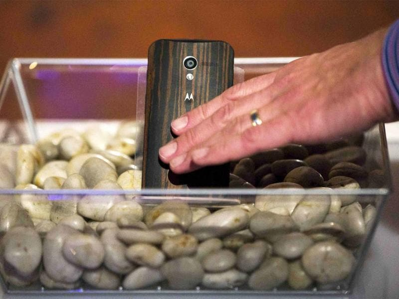Rick Osterloh, Senior Vice President of Product Management for Motorola, reaches down to touch a phone with a wooden back on it at a launch event for Motorola's new Moto X phone in New York. Photo: Reuters/Lucas Jackson