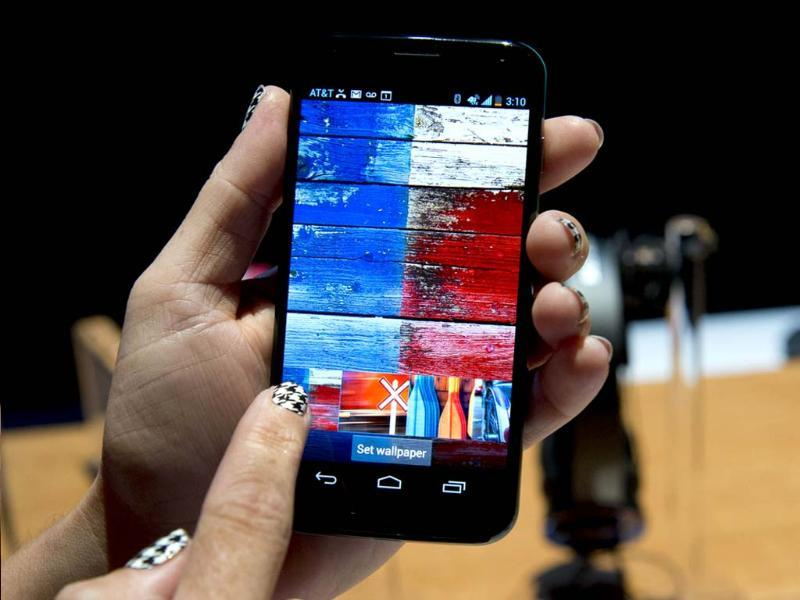 A Motorola employee demonstrates Motorola's Moto X as the American-manufactured smartphone is unveiled at a news conference in New York. Photo: AFP/Don Emmert