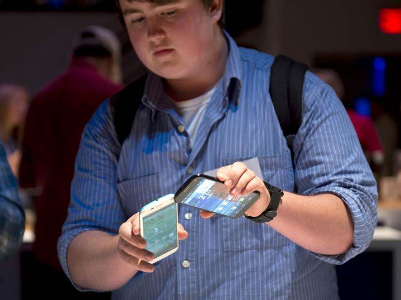 A member of the media tranfers data between two of Motorola's Moto X as the American-manufactured smartphone is unveiled at a news conference in New York. Photo: AFP/Don Emmert