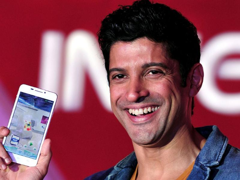 Farhan Akhtar poses with the new Intex Aqua i7 phone at the launch event in Mumbai. Photo: AFP/Indranil Mukherjee