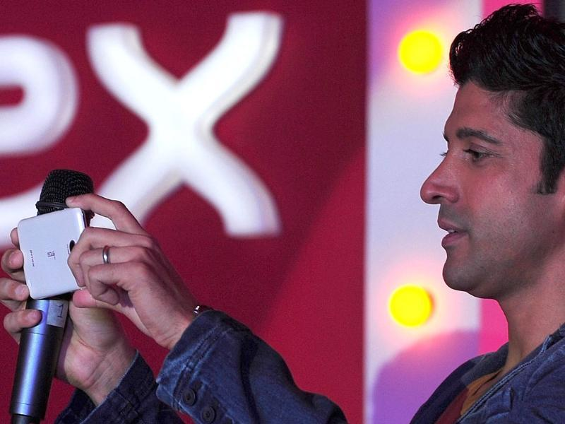 Farhan Akhtar takes a photograph with the new Intex Aqua i7 phone at a launch event in Mumbai. Photo: AFP/Indranil Mukherjee