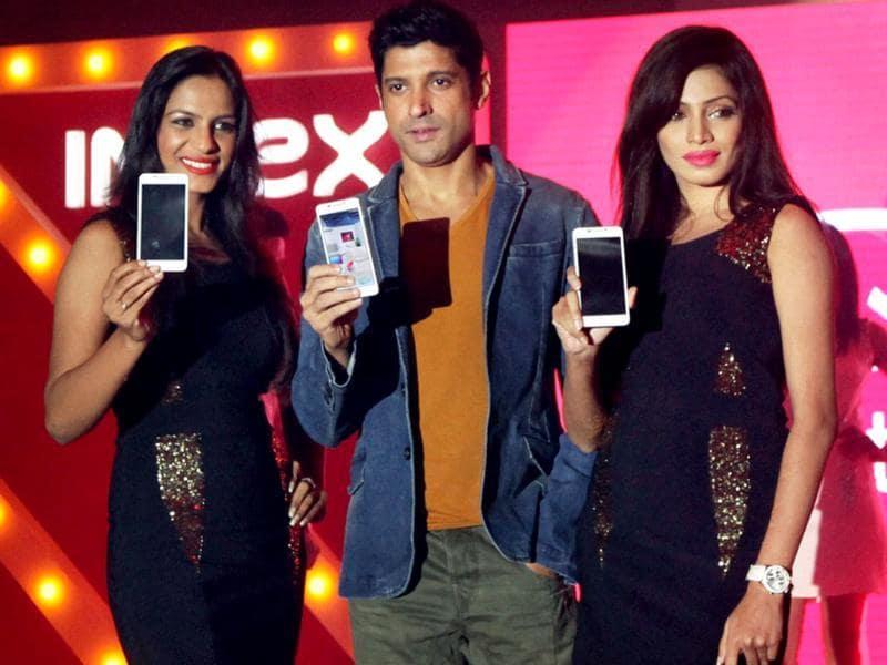 Farhan Akhtar with models during launch of Intex smartphones in Mumbai. Photo: PTI/Santosh Hirlekar