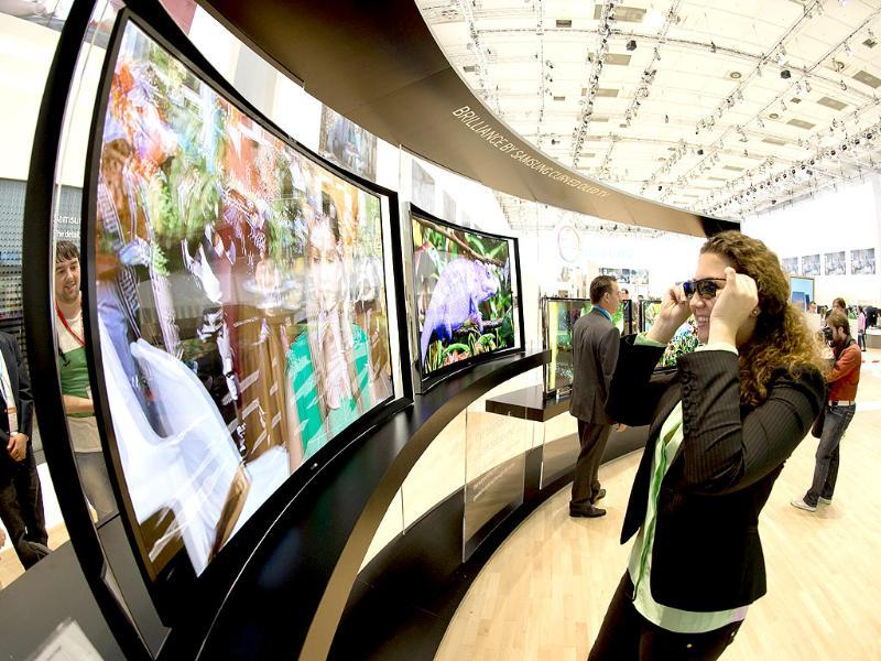 A woman looks at a curved OLED TV screen with 3D glasses at the booth of electronics giant Samsung at the 53rd IFA electronics trade fair in Berlin. Photo: AFP / Odd Andersen