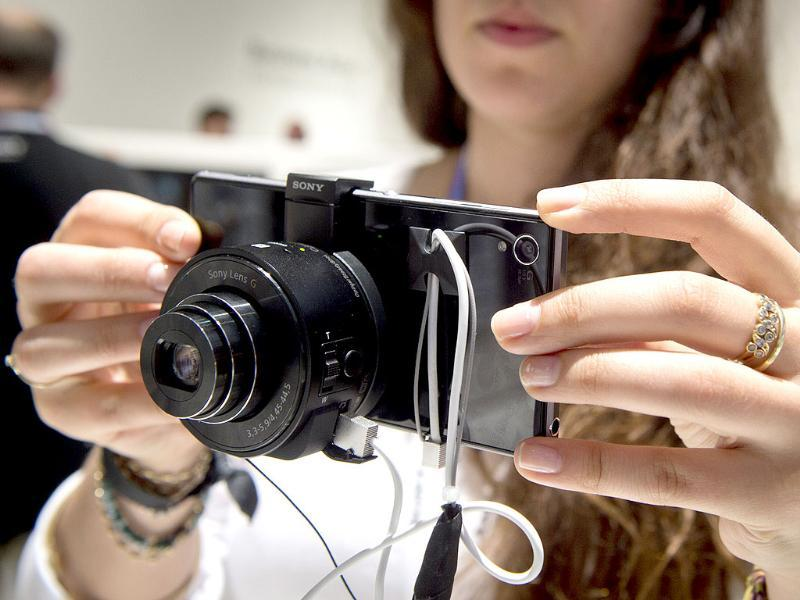A woman holds a camera that can be attached to a smart phone or tablets using the display as a viewfinder at the Sony booth at the 53rd edition of the IFA electronics trade fair in Berlin . Photo: AFP / Odd Andersen
