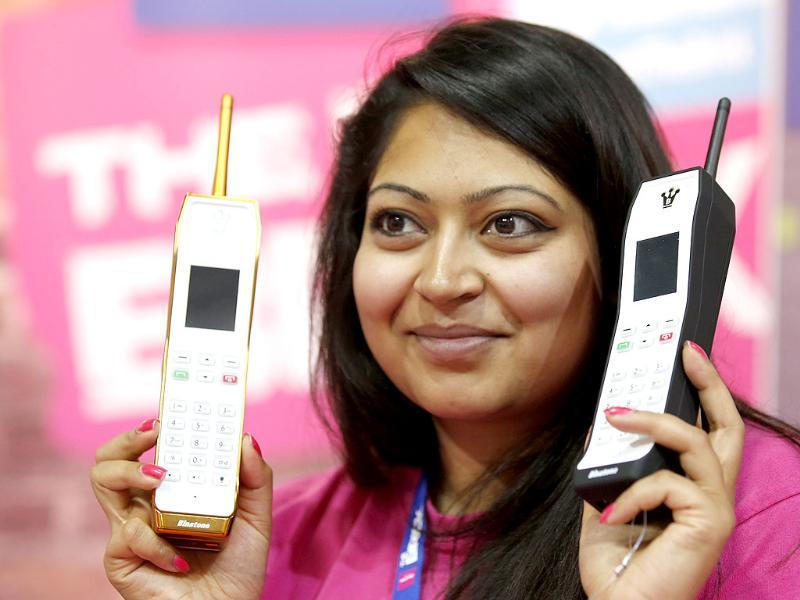 A model poses with retro-style The Brick mobile phones at booth of Binatone at the IFA consumer electronics fair in Berlin. Photo: Reuters/Fabrizio Bensch