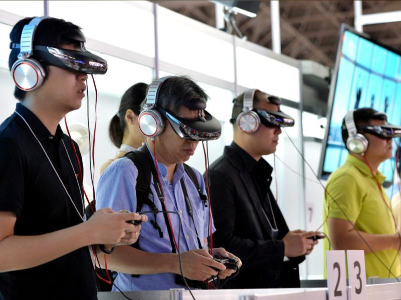 Visitors wear Japanese electronics giant Sony's new head mount display (HMD) 'HMZ-T3' to play videogames at the Tokyo Game Show in Chiba, in suburban Toky. Photo: AFP / Yoshikazu Tsuno