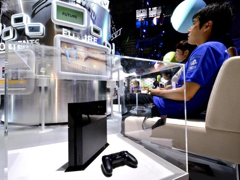 A visitor plays a videogame next to a display case containing Japanese videogame giant Sony Computer Entertainment's PlayStation 4 (L) at the Tokyo Game Show in Chiba. Photo: AFP / Yoshikazu Tsuno