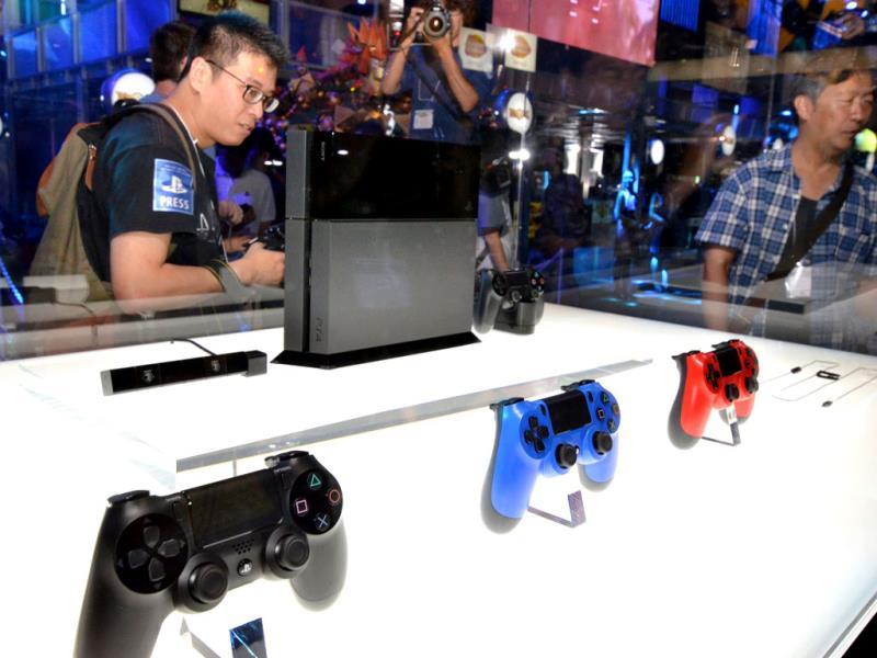 Visitors look at a display case containing Japanese videogame giant Sony Computer Entertainment's PlayStation 4 at the Tokyo Game Show in Chiba. Photo: AFP / Yoshikazu Tsuno