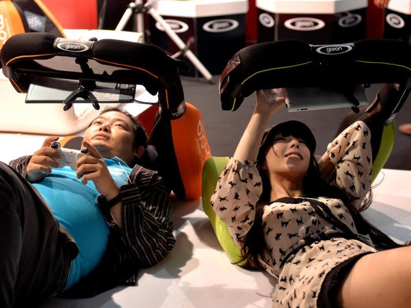 Visitors lay on pillows to play the videogame console and tablet holder 'Goron', produced by Japan's Sanyo Precision at the Tokyo Game Show in Chiba, suburban Tokyo. Photo: AFP / Yoshikazu Tsuno