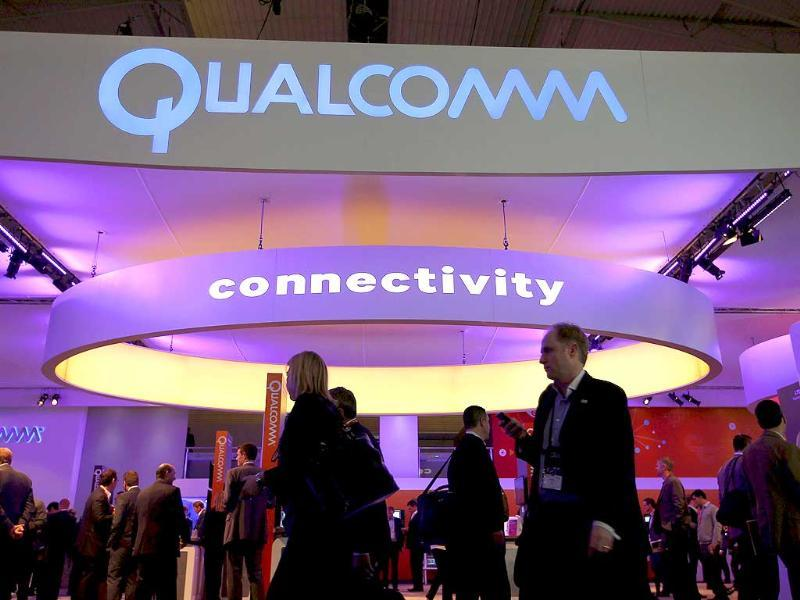Visitors walk past the Qualcomm stand at the Mobile World Congress in Barcelona. (Reuters photo)