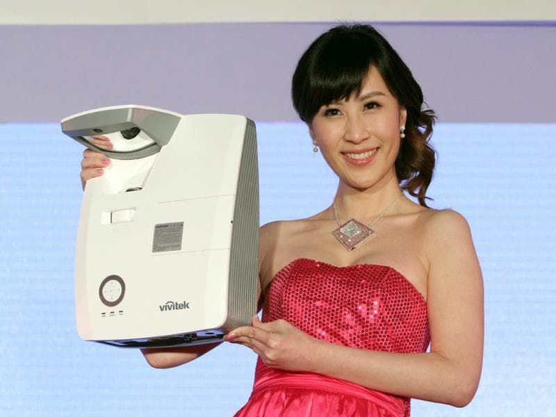 A model displays Delta's D755WTIR Ultra-short throw interactive projector during a press event on the eve of the Computex Taipei. Photo: AP/Chiang Ying-ying