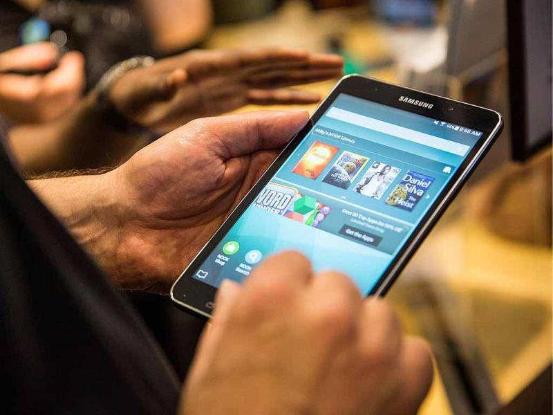 People play with the new Samsung Galaxy Tab 4 Nook at a media event in New York City. The new tablet has a 7-inch screen and will cost $179. Photo: Andrew Burton/Getty Images/AFP