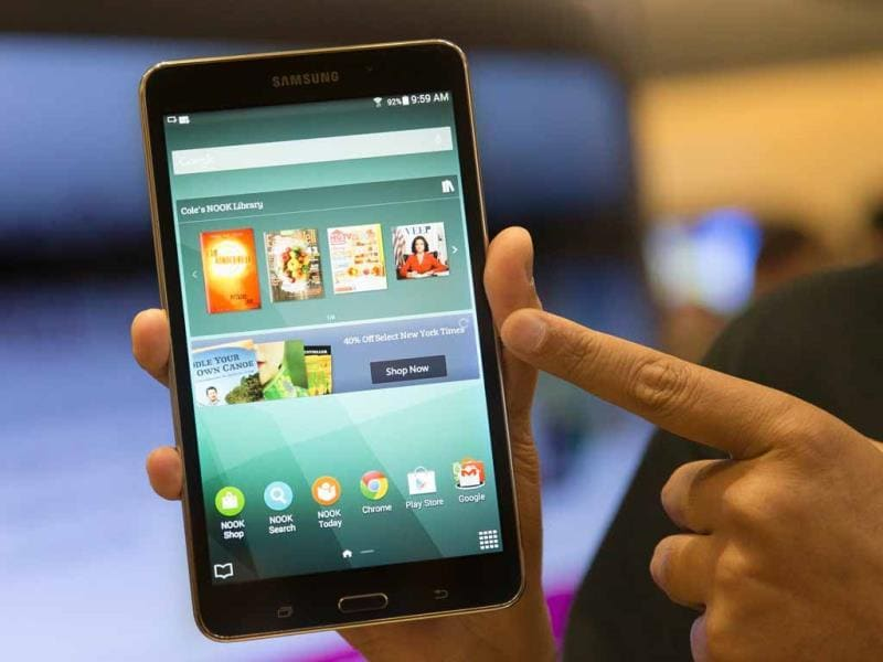 A brand ambassador handles a new Samsung Galaxy Tab 4 Nook during the unveiling of the co-branded tablet that will replace B&N's Nook in New York. (AP Photo/John Minchillo)