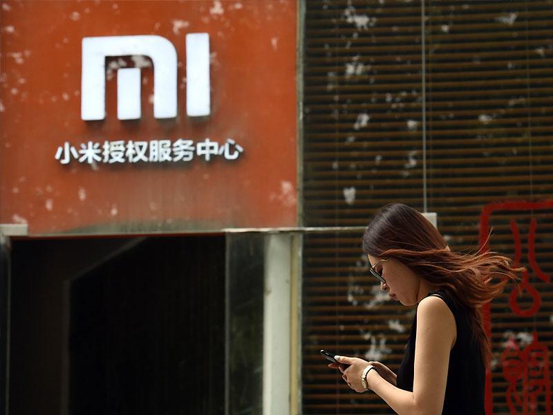 A woman walks past a Xiaomi logo outside a Xiaomi service center in Beijing. Photo: AFP
