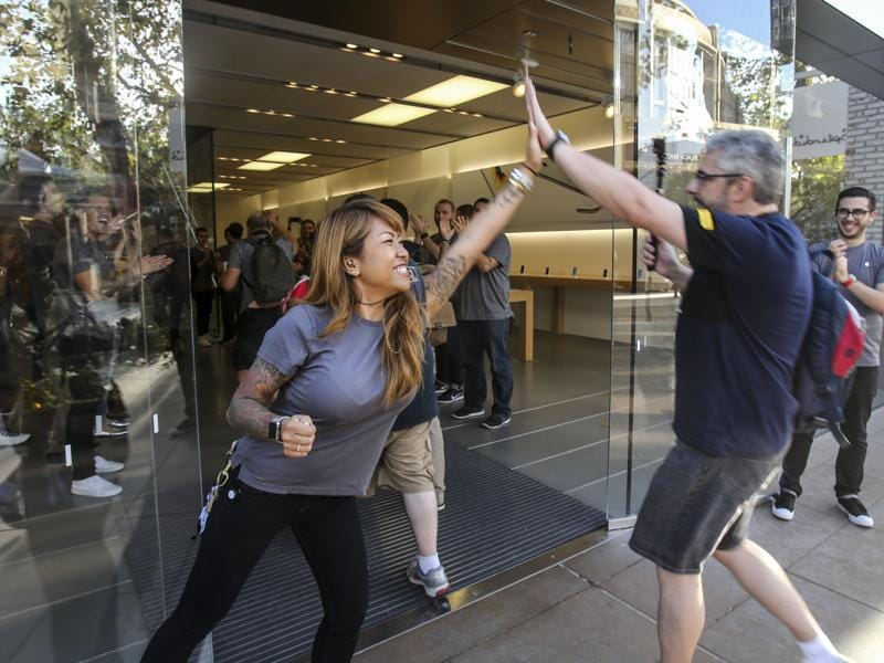 An Apple employee greets a customer, right, entering to buy the Apple iPhone 6s and iPhone 6S Plus at the Apple store in Los Angeles. (AP Photo)