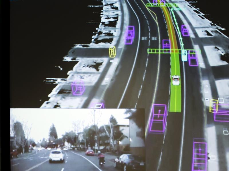 Video captured by a Google self-driving car, inset, is coupled with the same street scene as the data is visualised by the car.  (REUTERS)