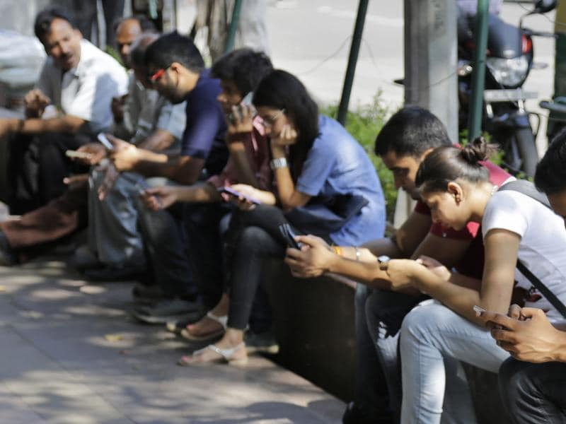 People use their mobile phones in New Delhi.