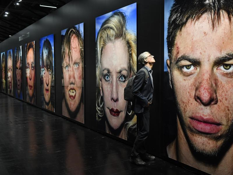 A visitor passes a street photography portraits by US artist Bruce Gilden at an exhibition on the sidelines of Photokina.  More than 1000 exhibitors from 51 countries will show the latest developments in digital imaging From September 20 to September 25 at the Cologne fair halls. (Martin Meissner / AP )