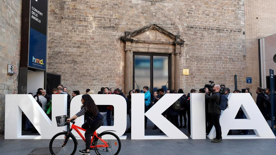 FILE PHOTO: A cyclist rides past a Nokia logo during the Mobile World Congress in Barcelona, Spain February 25, 2018. REUTERS/Yves Herman/File Photo