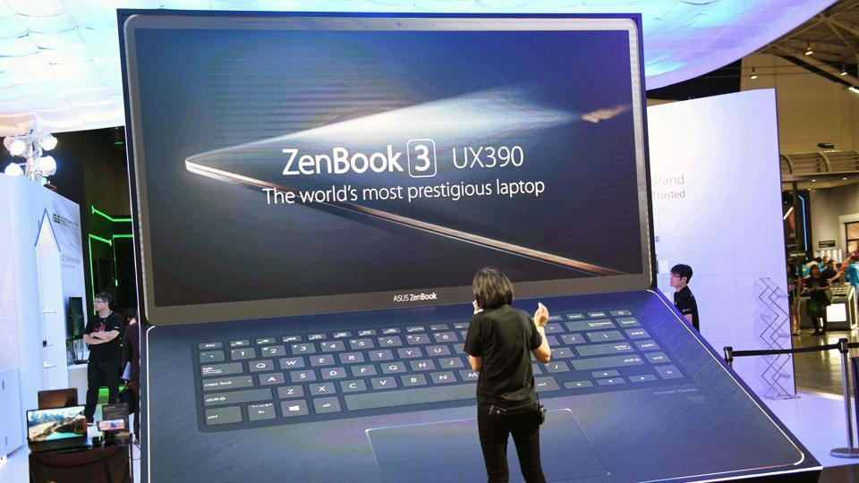 A staff of Taiwan's Asus checks a giant laptop mockup of a ZenBook computer during Computex 2018 at the Nangang Exhibition Center in Taipei on June 5, 2018.