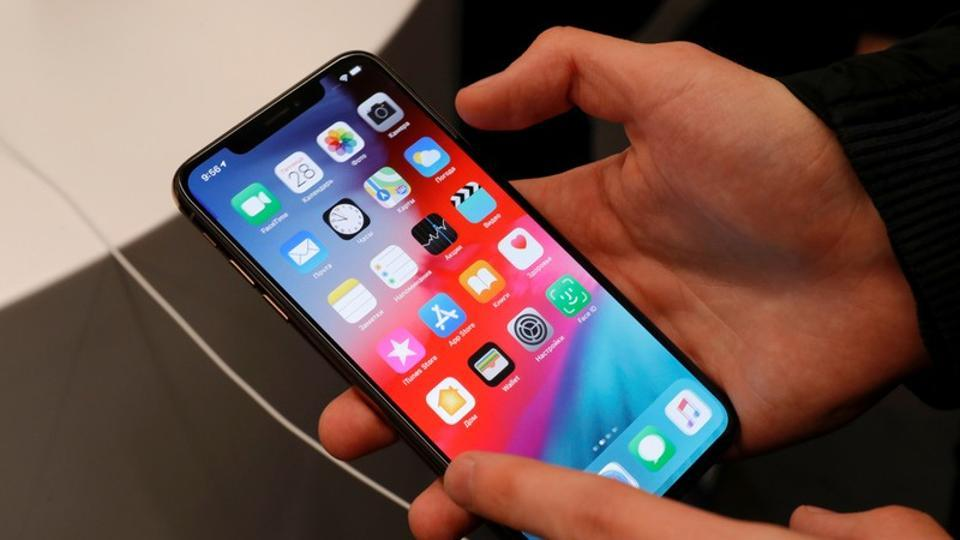 FILE PHOTO: A customer tests a smartphone during the launch of the new iPhone XS and XS Max sales at