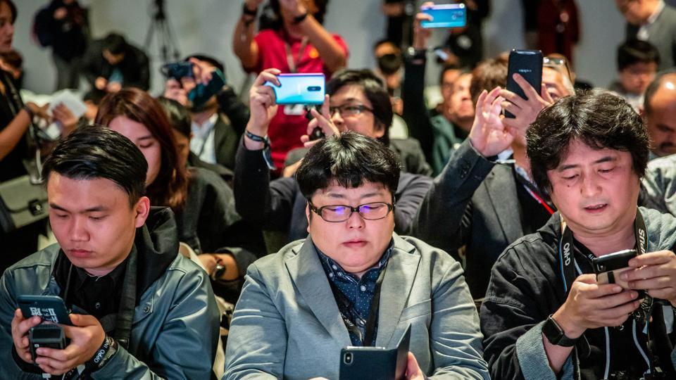 Attendees check their smartphone devices during a Guangdong Oppo Electronics Co. launch event ahead of the MWC Barcelona in Barcelona, Spain, on Saturday, Feb. 23, 2019.