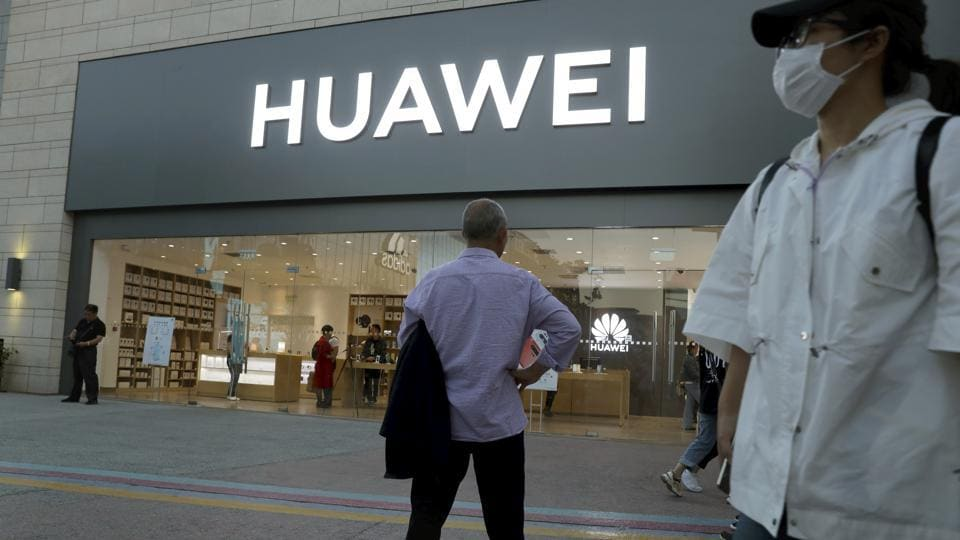 In this photo taken Monday, May 20, 2019, a man stands outside a Huawei store in Beijing. The Financial Times reported Friday, May 31, 2019 that tech giant Huawei has ordered its employees to cancel technical meetings with American contacts and has sent home numerous U.S. employees working at its Chinese headquarters.