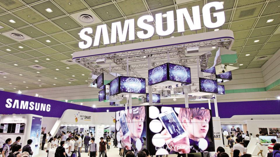 Visitors walk past the Samsung Electronics Co. booth at the World IT Show 2012 in Seoul, South Korea.