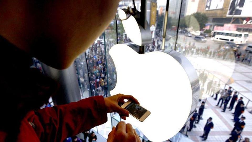 A man takes a photograph using his iPhone of members of the public entering a new Apple store during the official opening in Beijing.